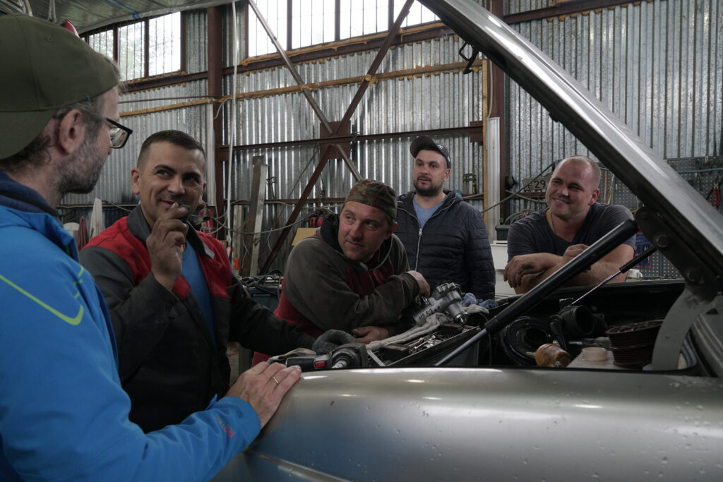 Aleksandr Sologubov (links) beim Autoservice mit Meister Ruslan und seinen Kollegen. Foto: Frank Gaudlitz